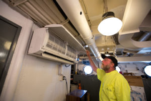Caption: Glenn Davis, a heating and cooling technician with Jacksonville Heating Contractors, inspects a Carrier ductless air conditioner recently installed aboard the USS North Carolina.